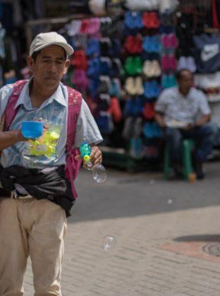 """Jabonero – Carabobo – Los niños aman ver las burbujas de jabón en el aire. Los tradicionales """"jaboneros"""" lo saben, y por esta razón hablar del producto está de menos. Para atraer a sus clientes, es necesario llamar la atención de los más chicos. Mantener con vida las burbujas es prioridad, y soplar a todo pulmón es su mejor estrategia financiera."""