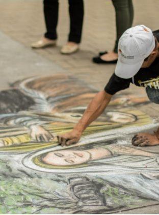 """Natividad – La calle es un lienzo para un artista callejero que pinta """"la natividad"""" con tizas de colores pastel. Es noviembre, diciembre se avecina y los paisas se apresuran con los preparativos y las tradiciones, al igual que la lluvia de ese día. Para la memoria esta pieza de arte."""