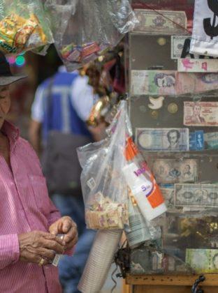 Sujeto del cambio. Durante las ventas de mekato, chicles y chucherías es común encontrar billetes falsos y monedas extranjeras. Los venteros toman medidas y afilan los ojos para descubrir las posibles estafas. En la fotografía, un hombre exhibe sus hallazgos, orgulloso, en el respaldo de su caseta.