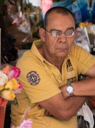 """Floristero – Junín – Los floristeros son admirados por su paciencia para vender. El hombre de la fotografía espera en silencio y de vez en cuando le habla a las flores como si fueran sus hijas . """"No demoran en llegar, bellezas""""."""